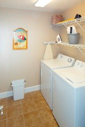 Large laundry room with new washer and dryer, iron and ironing board.